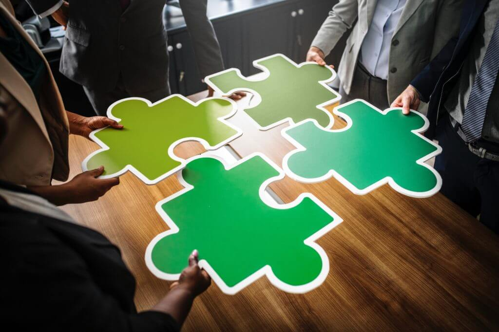 Business people with puzzle pieces.
