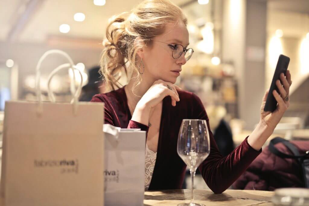 Woman who is looking at phone while shopping