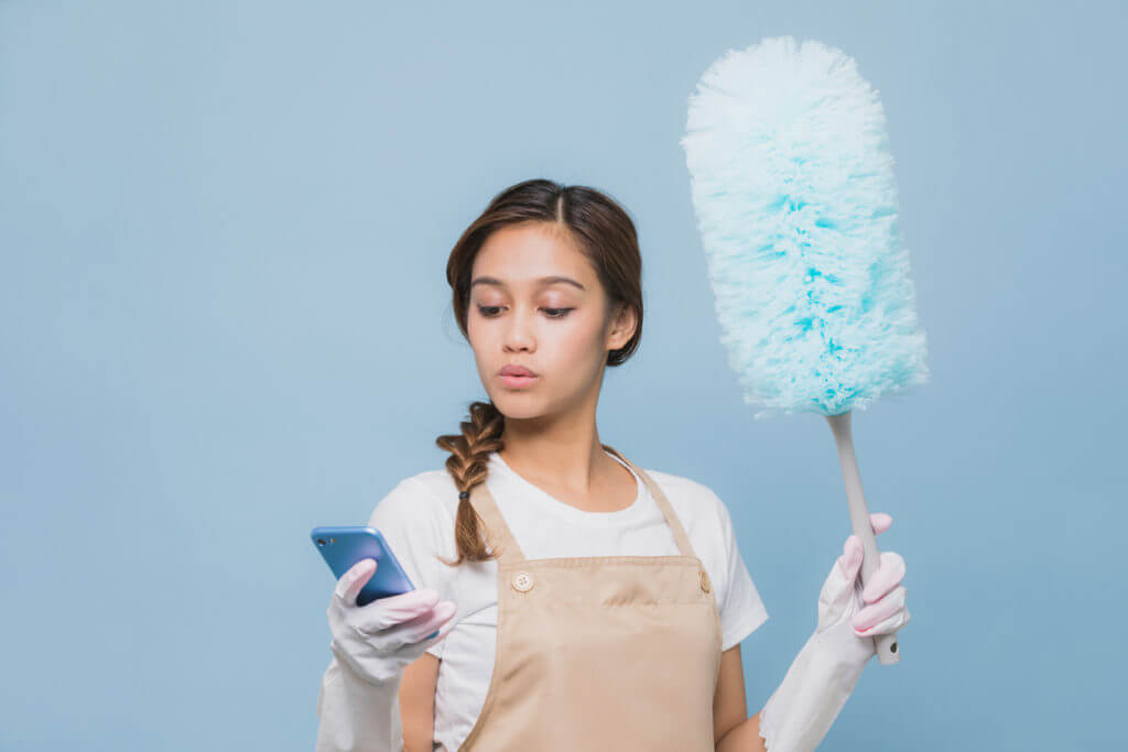 Woman looking at phone while house cleaning