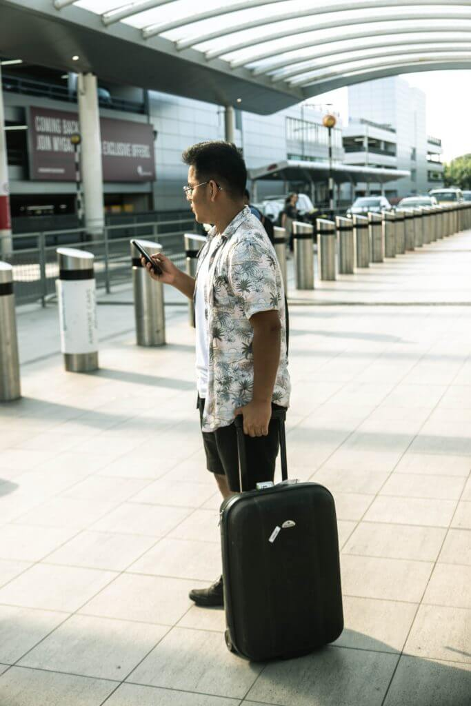 Hotel guest with luggage and checking phone.