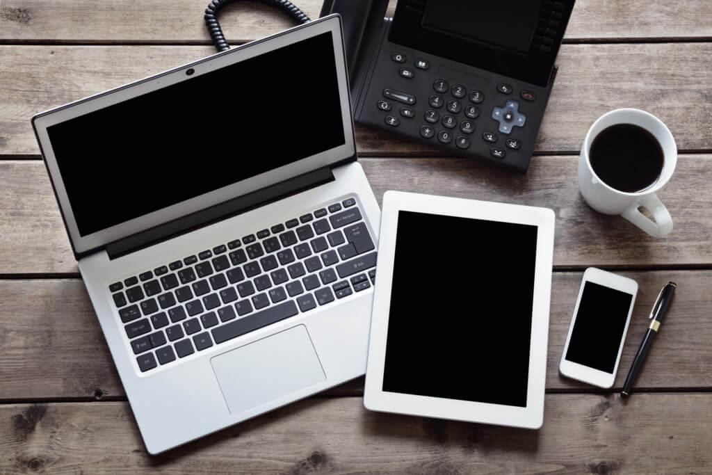 Laptop, desk phone, tablet, smartphone on desk.