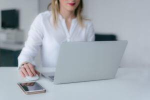 Woman texting at computer.