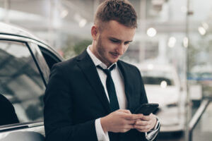 Car salesperson using SMS automotive to reach customers