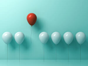 A red ballon amongst blue balloons shows how business texting services help you stand apart