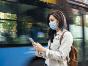 Masked woman receiving a business SMS message while waiting for bus