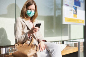 Woman Using Business SMS During COVID-19 Mask Requirements