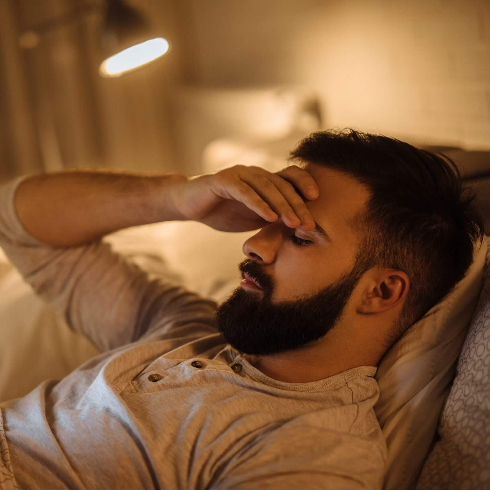 Man lying in bed using personal phone for business text messaging