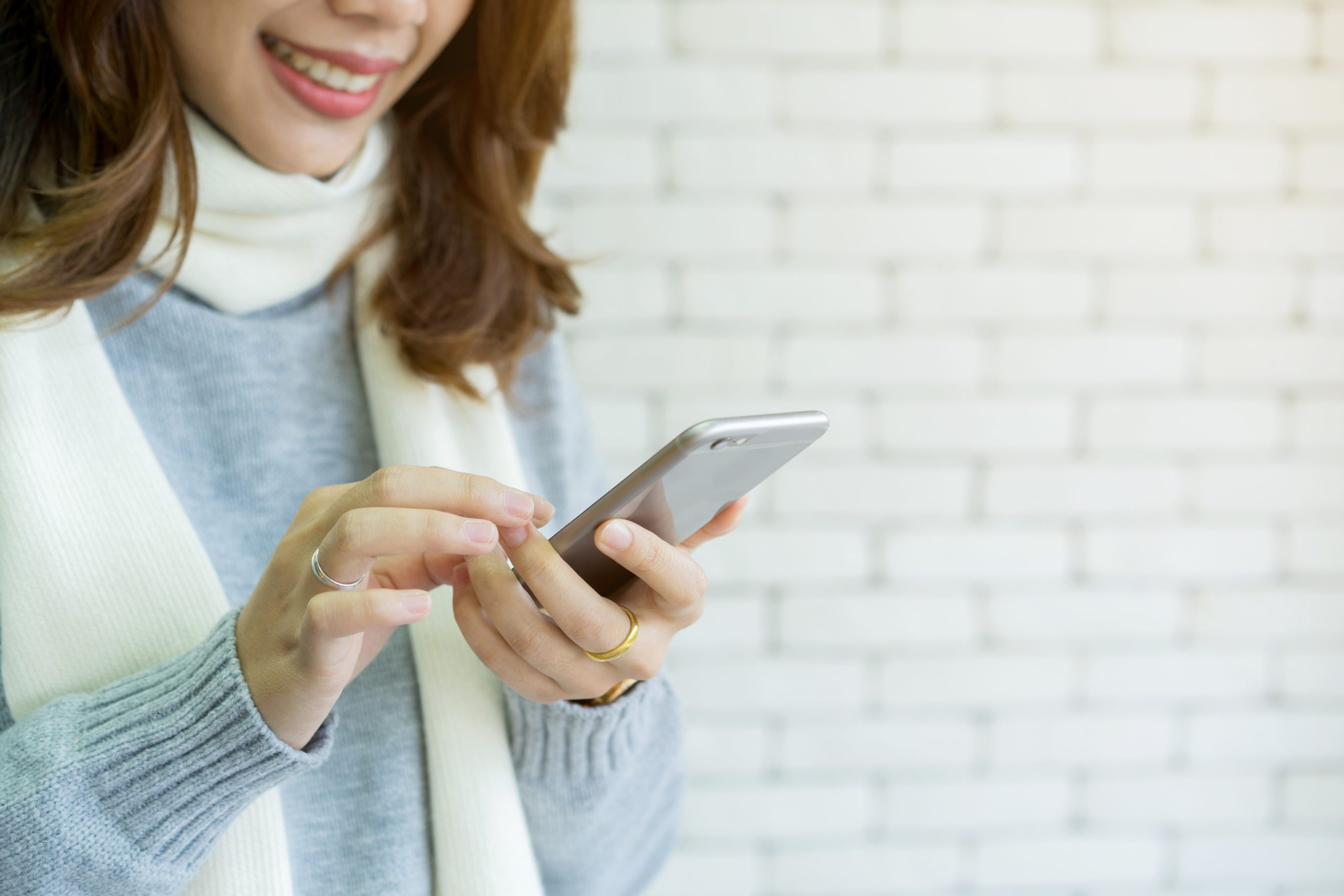 Woman in scarf texting using Conversational customer engagement