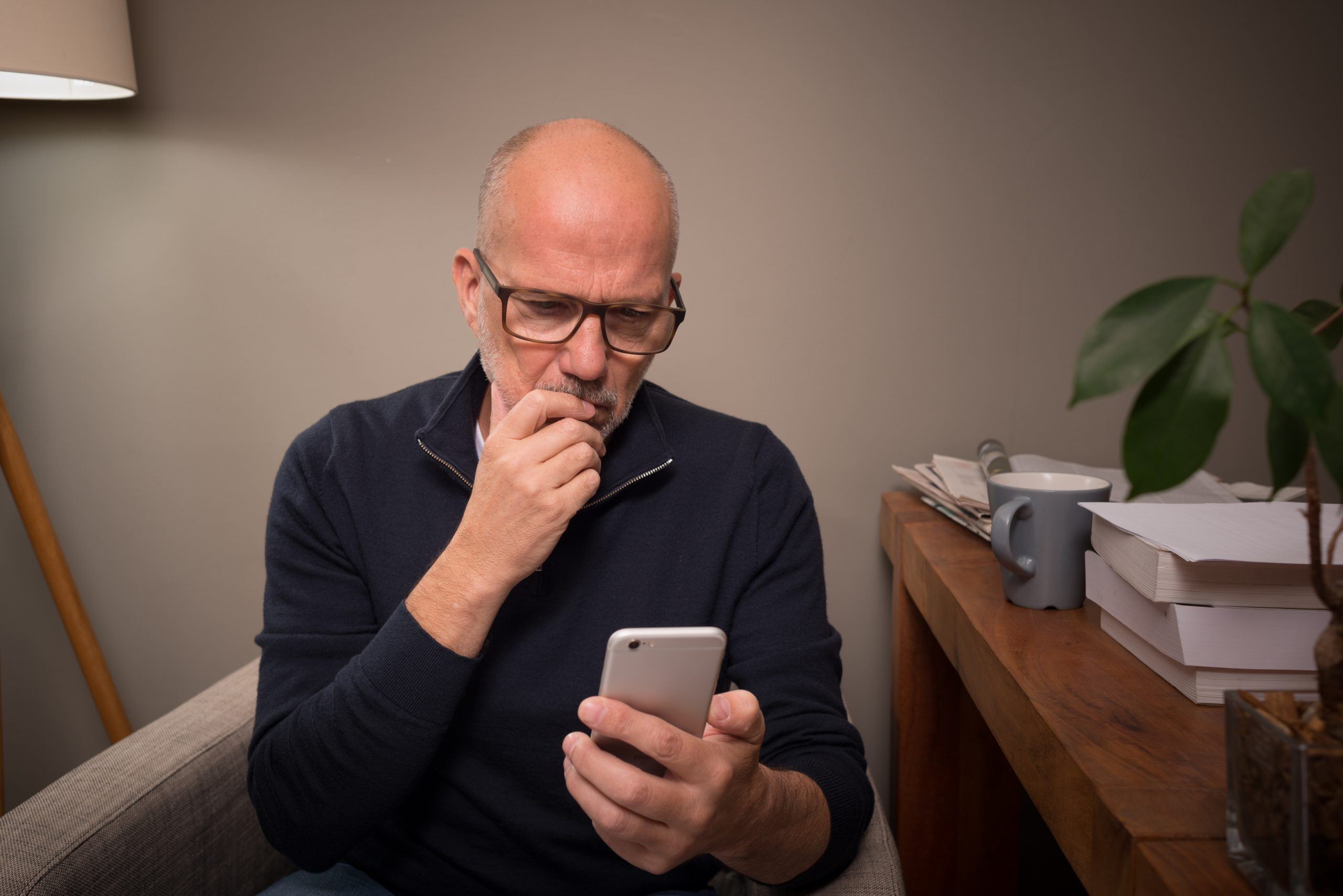 Concerned-looking man texting, meant to illustrate secure text messaging