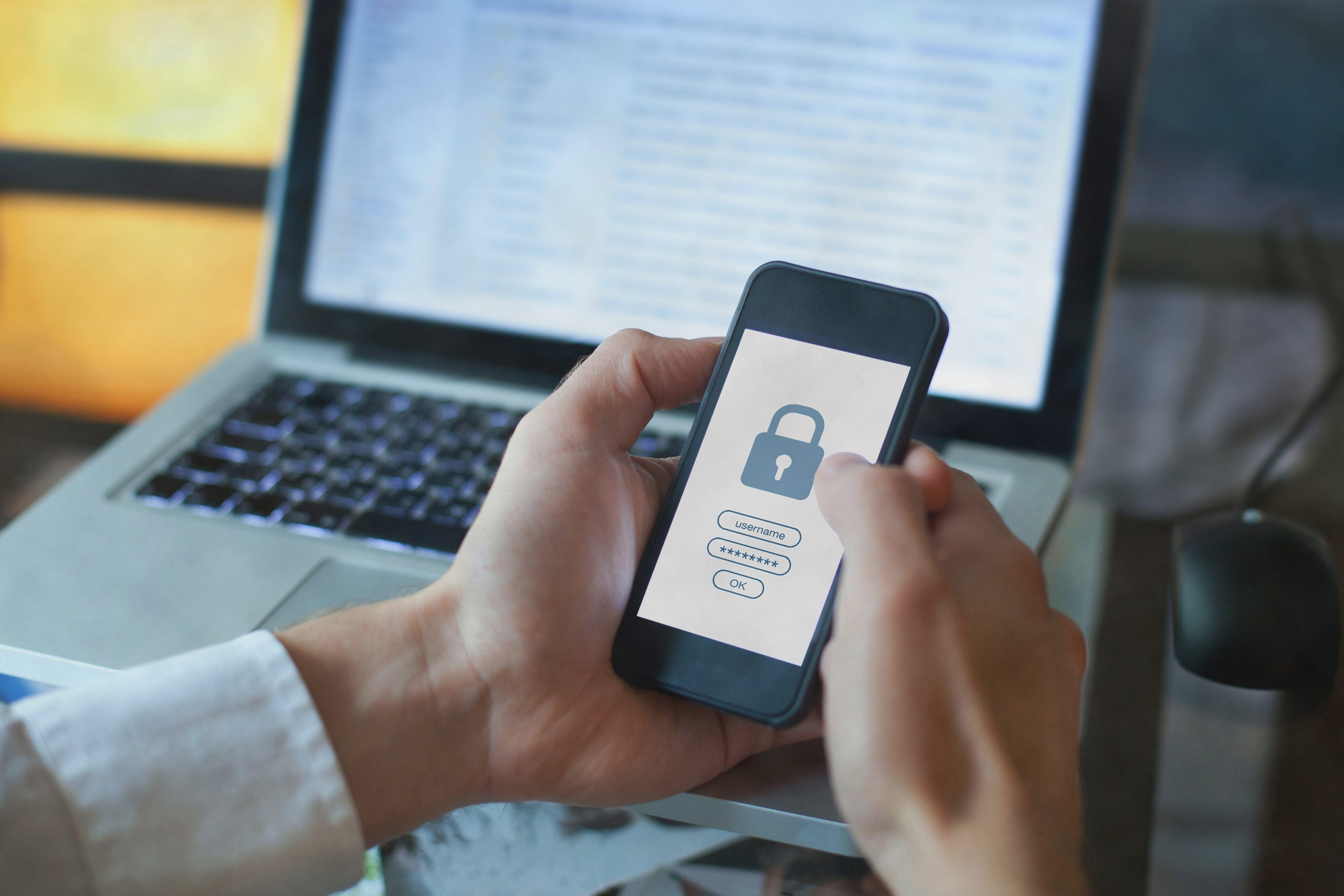 Hands holding phone with lock icon to show SMS security