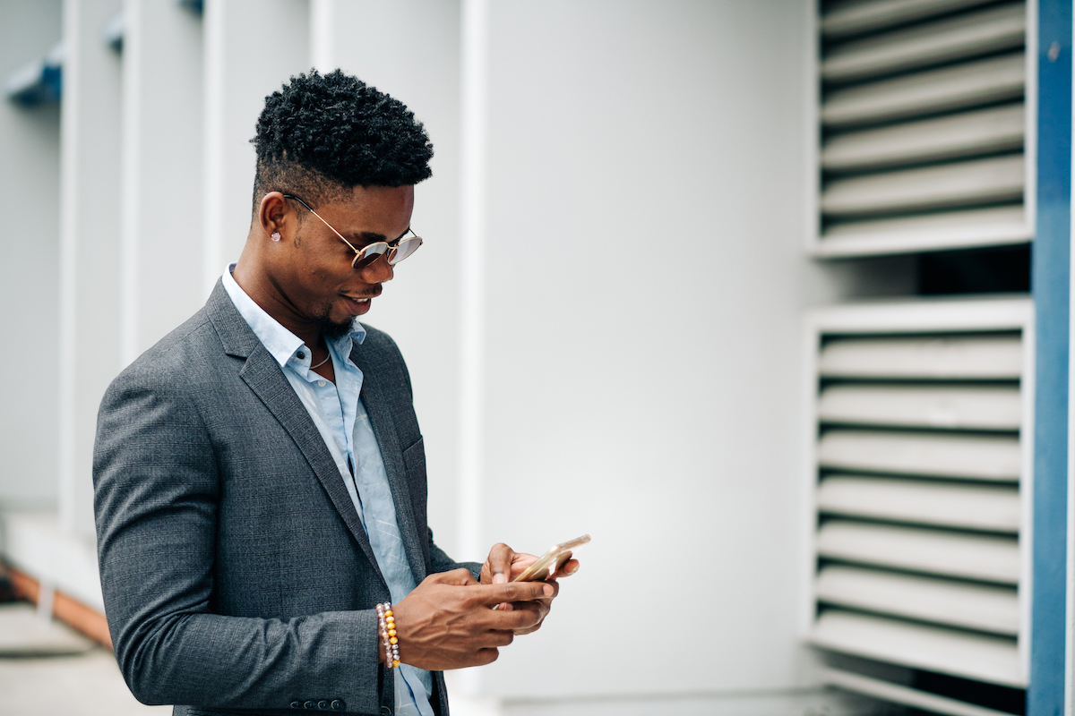 Businessman in sunglasses smiling down at phone while using business texting