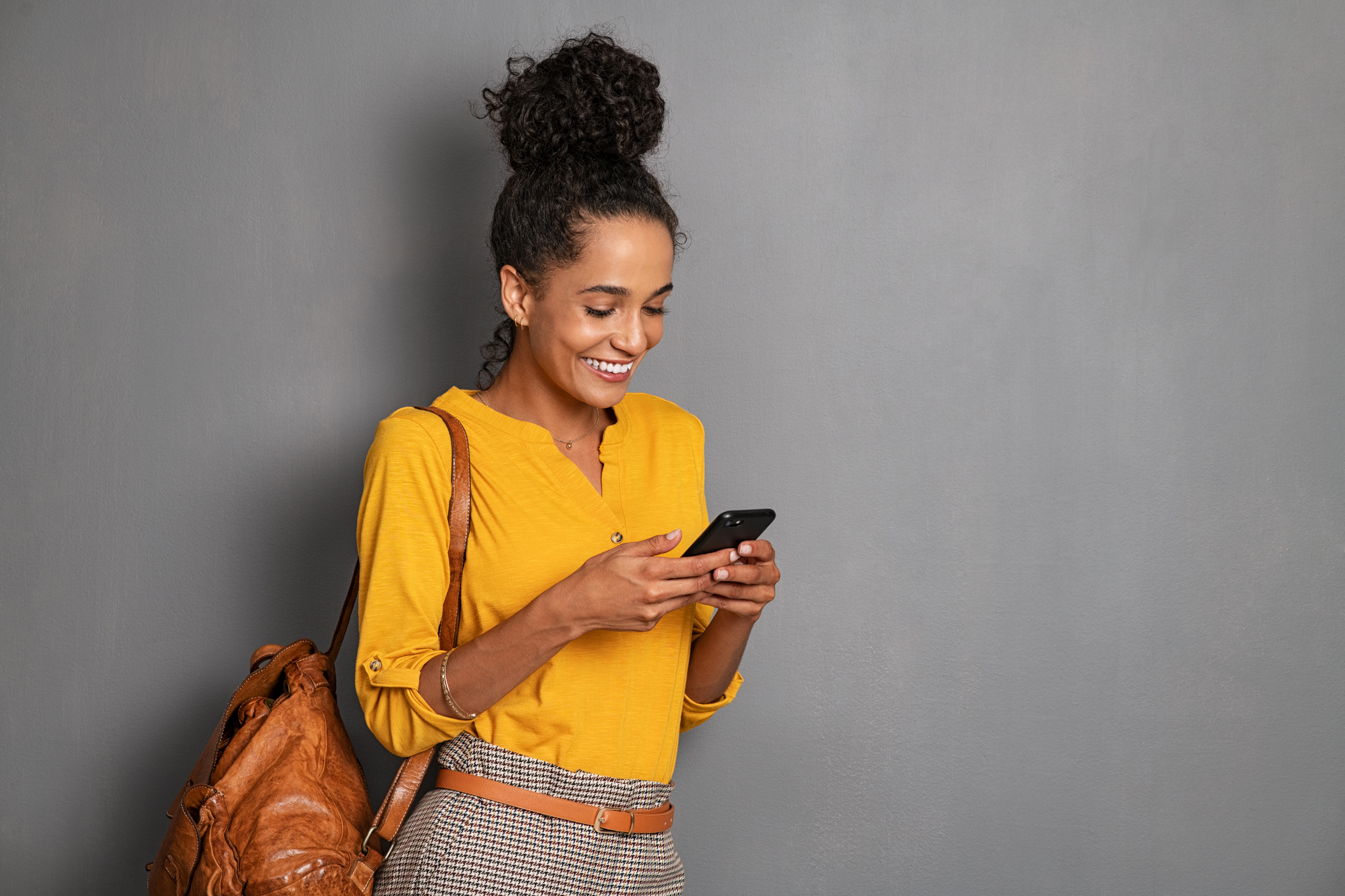 Woman in yellow learning against a wall and texting using conversational support