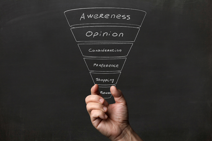 Hand holding up a marketing funnel, demonstrating how to build marketing funnels with business sms
